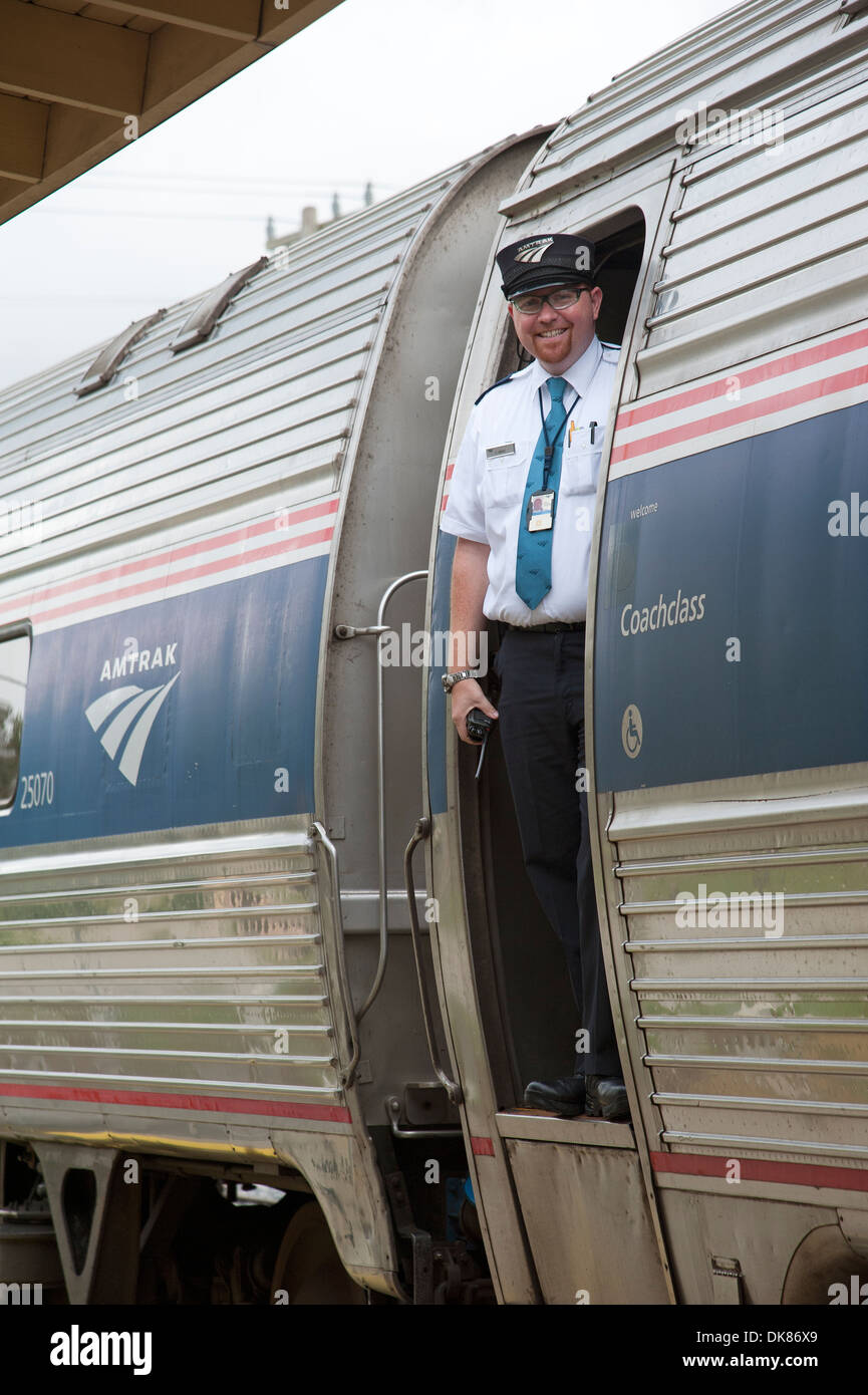 Smiling railroad conductor on Amtrak passenger train - Stock Image