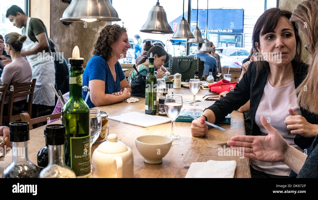 diners enjoy animated conversation at communal table in convivial atmosphere of trendy Le Pain Quotidien in midtown Manhattan - Stock Image