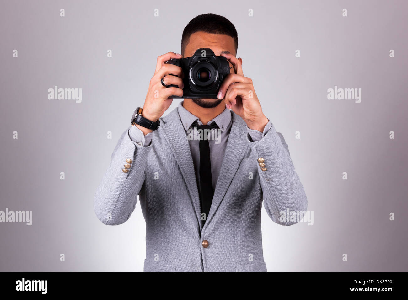 African american photographer holding a dslr camera, over gray background - Black people - Stock Image