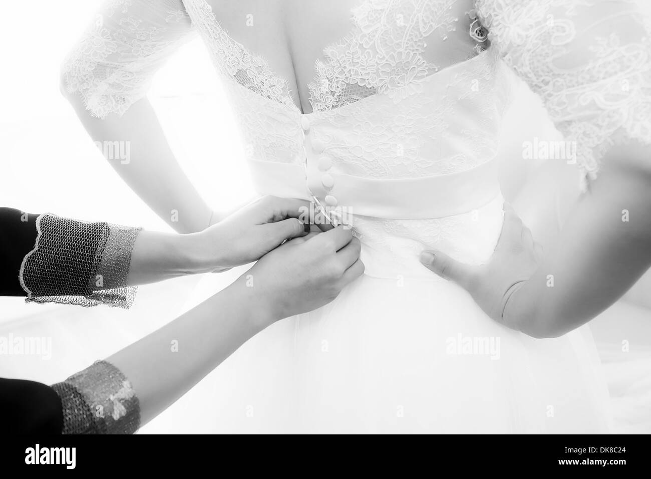 Bride getting dressed and buttoned - Stock Image