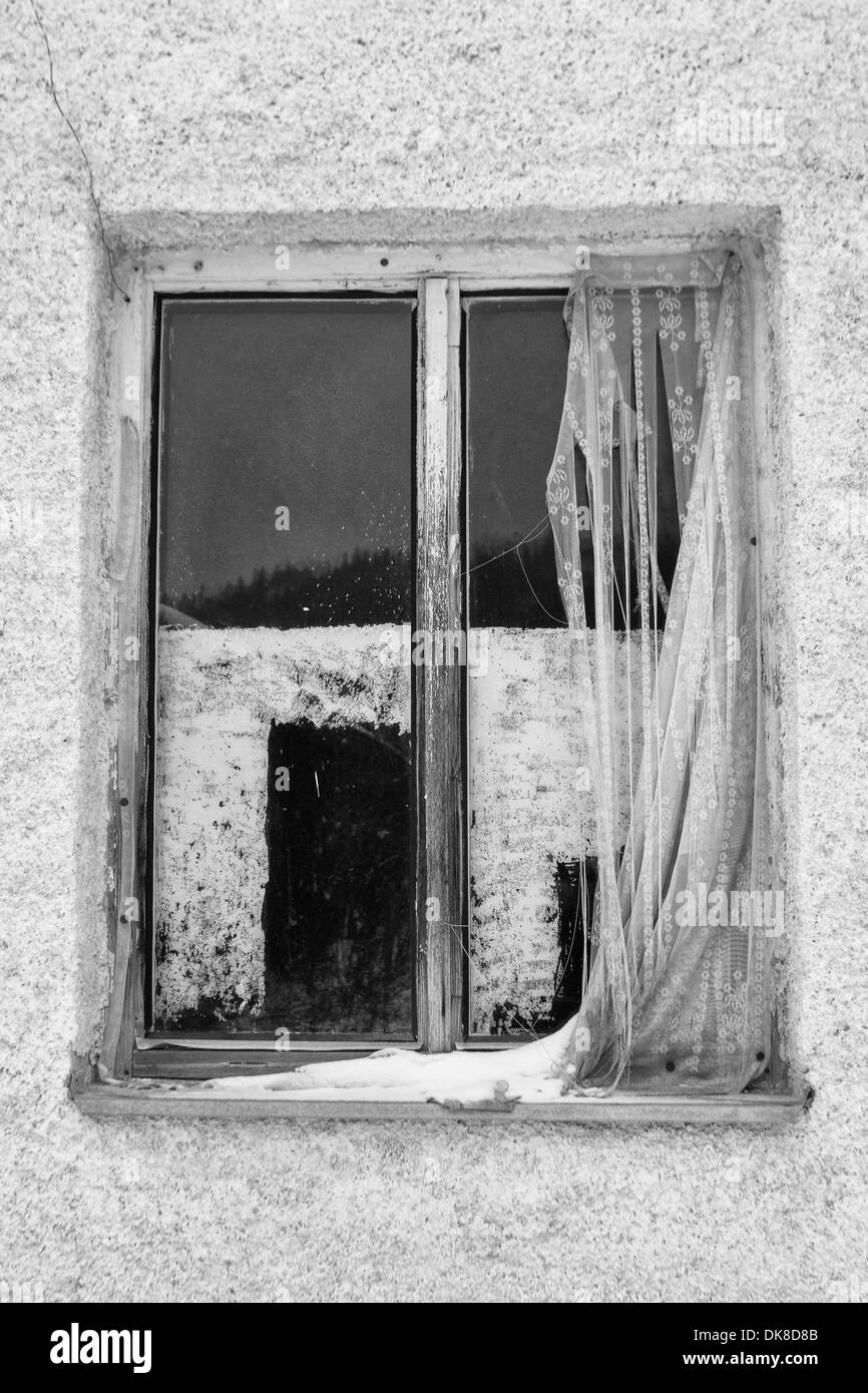 Old window with curtain outside on building - Stock Image