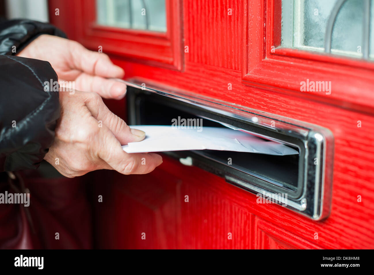Hand putting Letter in a red mailbox. - Stock Image