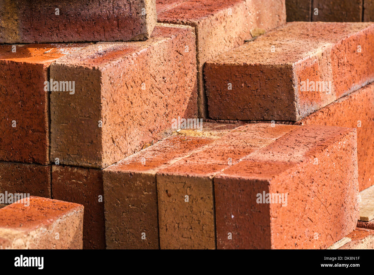 Stack of red bricks forms abstract geometric angular shapes - Stock Image