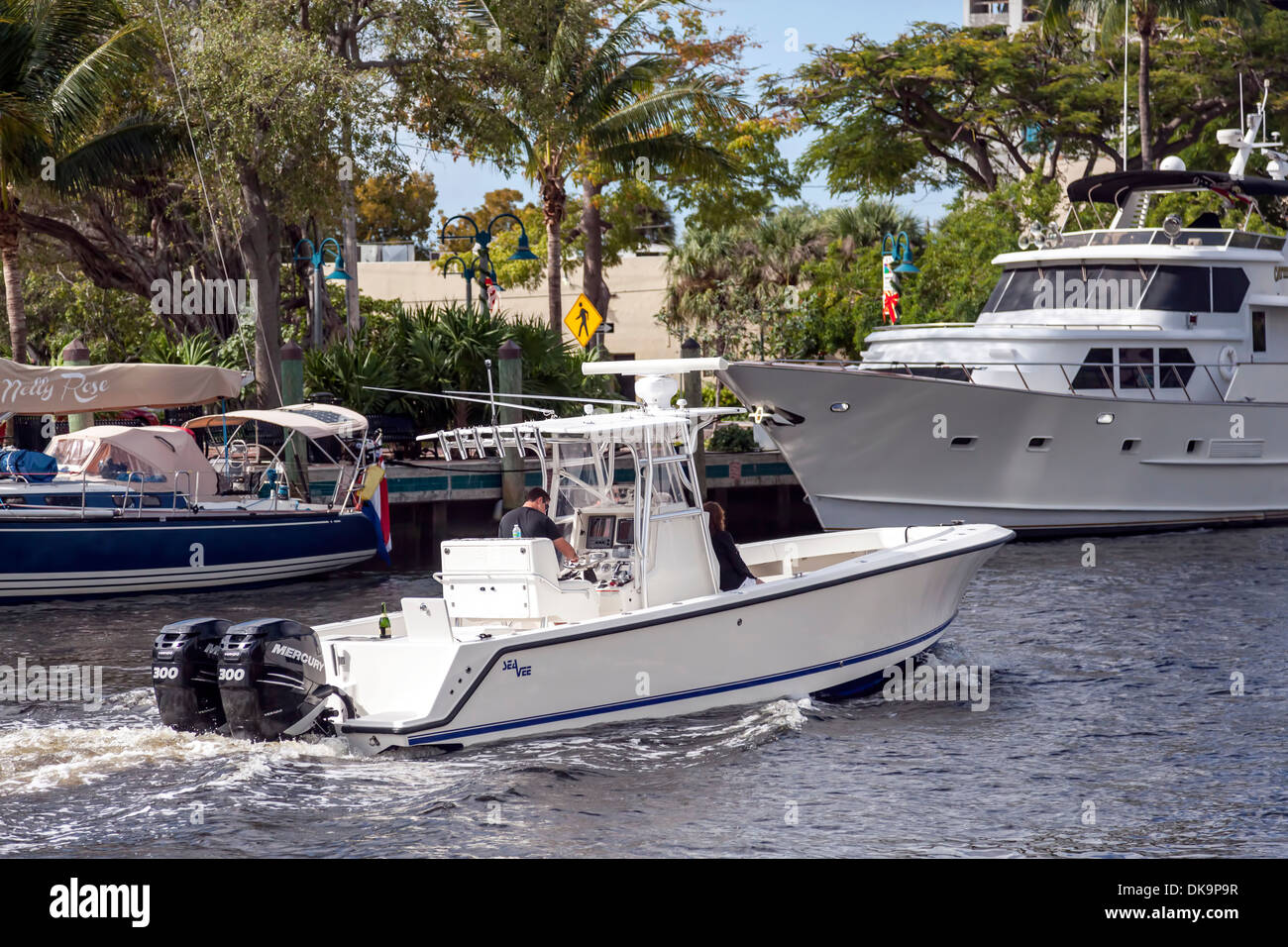 Couple cruising up the New River in a SeaVee 290 with dual Mercury 300 outboard motors, downtown Fort Lauderdale, Florida, USA. - Stock Image