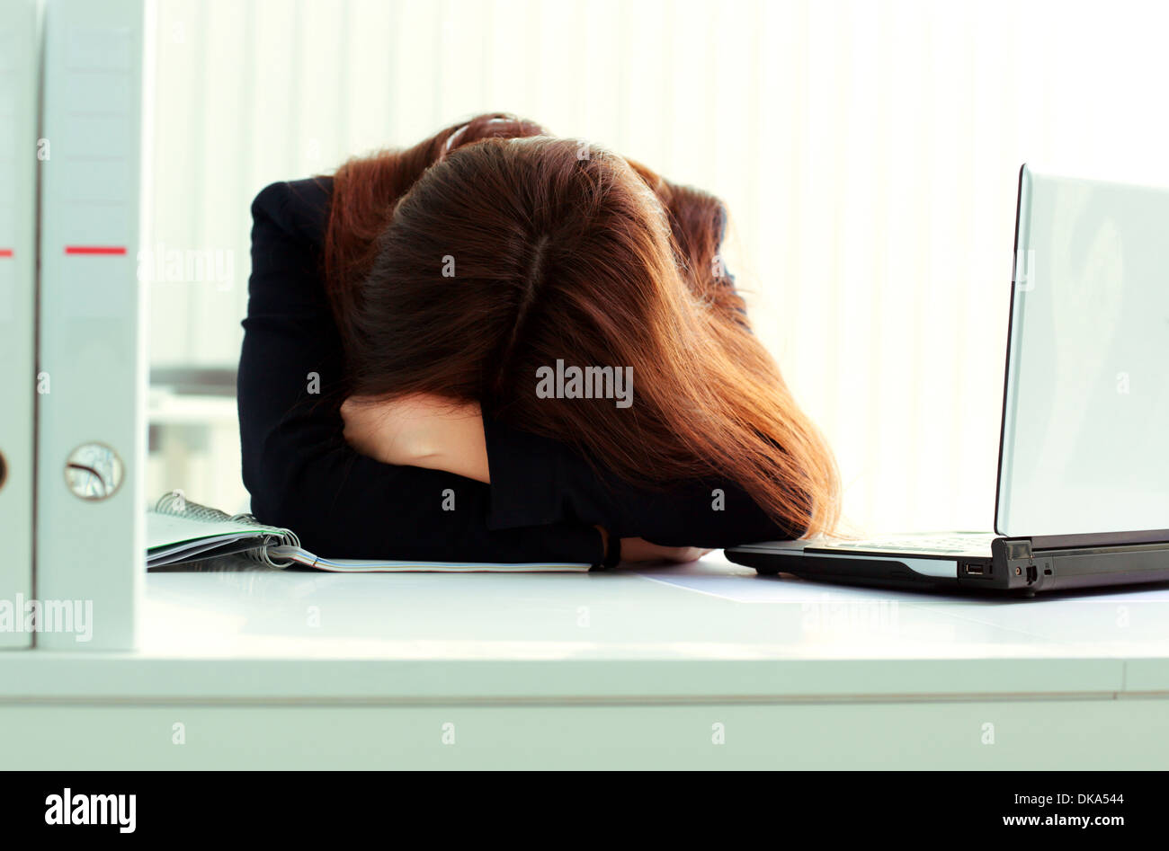 Young tired businesswoman sleeping at her workplace in office - Stock Image