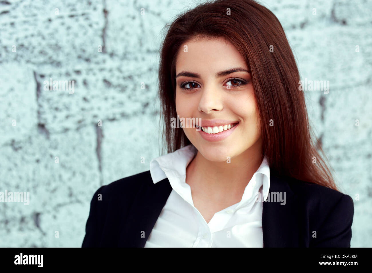 Closeup portrait of a young happy businesswoman near brick wall Stock Photo