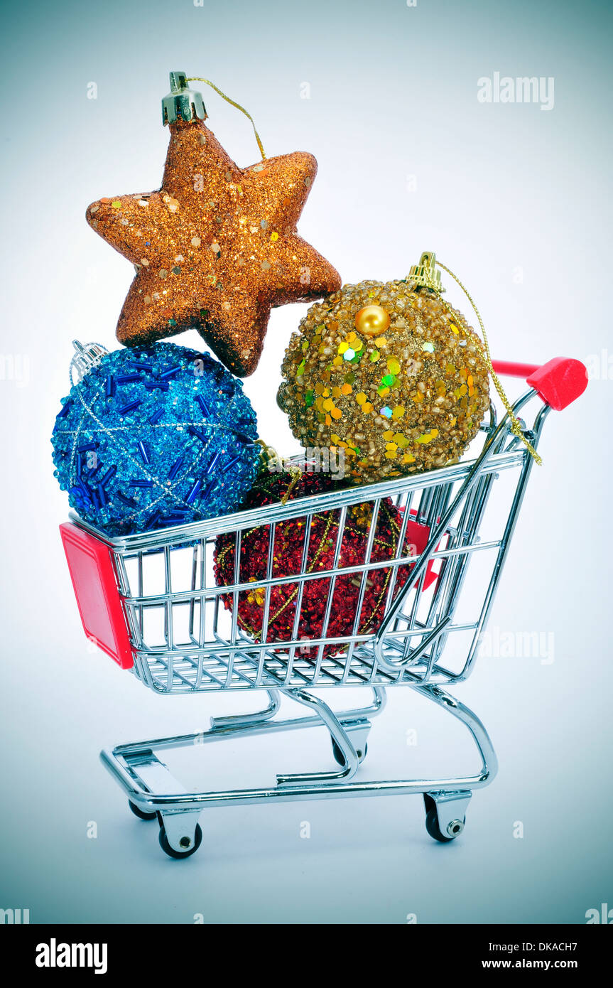 a pile of christmas ornaments in a shopping cart, depicting the christmas shopping concept - Stock Image
