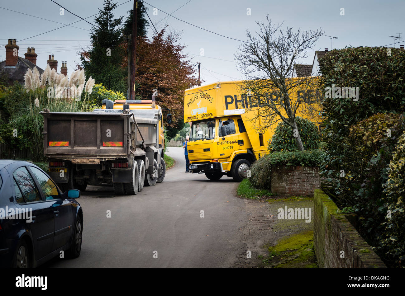 Driver assisting traffic flow during temporary rural congestion caused by a removal van working in small village lane in UK - Stock Image