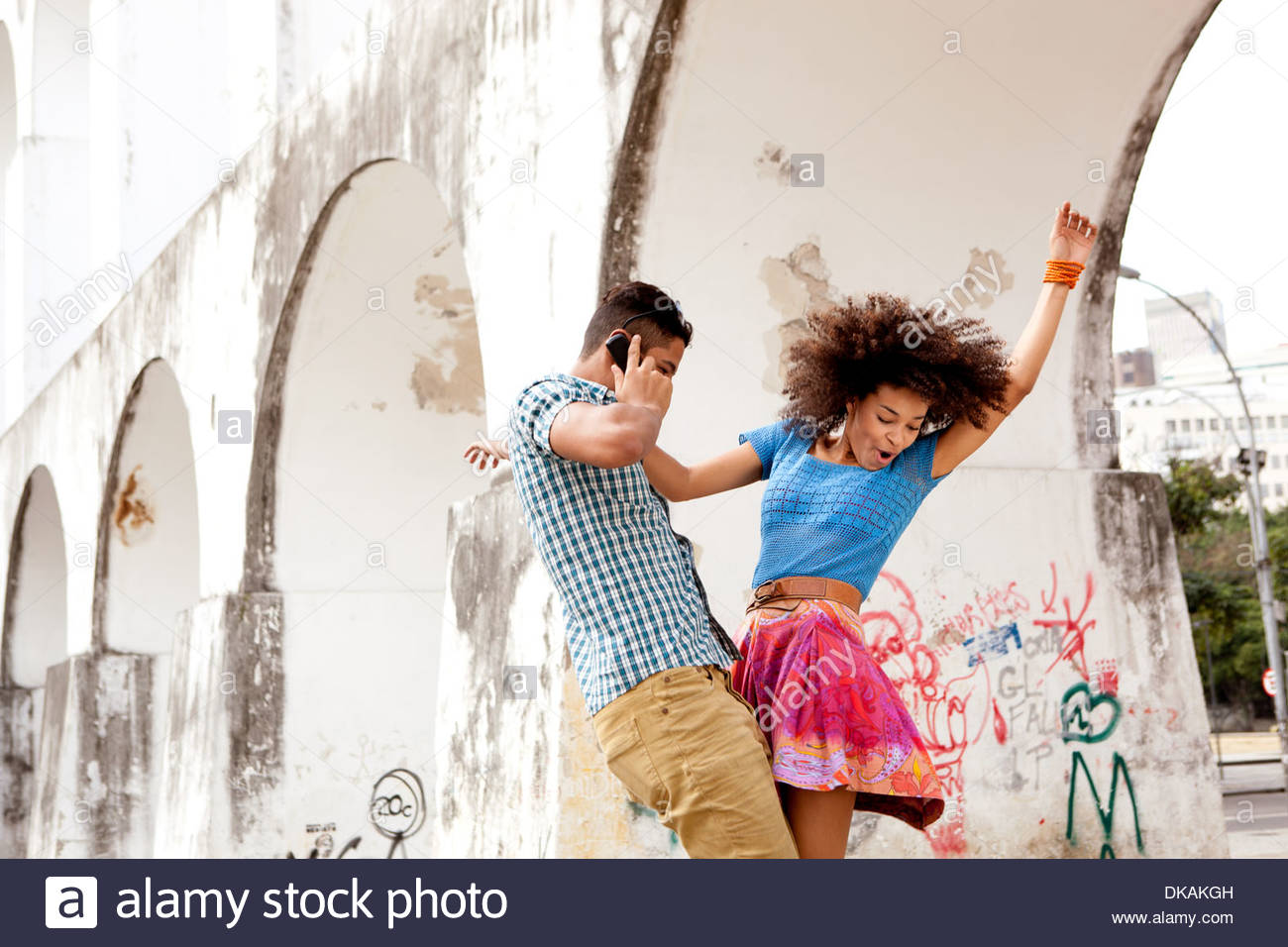 Young couple dancing in front of Carioca Aqueduct, man on phonecall, Rio, Brazil - Stock Image