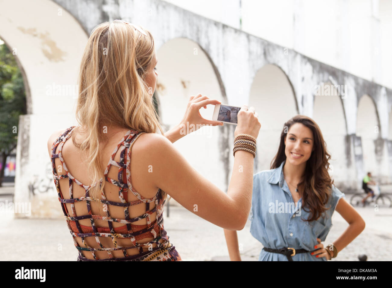 Young woman taking photograph of friend in front of Carioca Aqueduct, Rio de Janeiro, Brazil - Stock Image