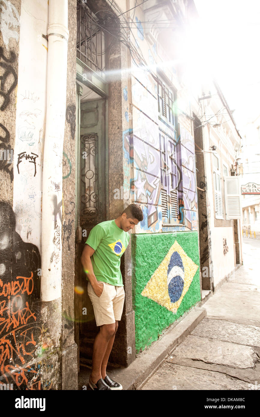 Young man wearing Brazil top standing in doorway next to Brazil flag - Stock Image