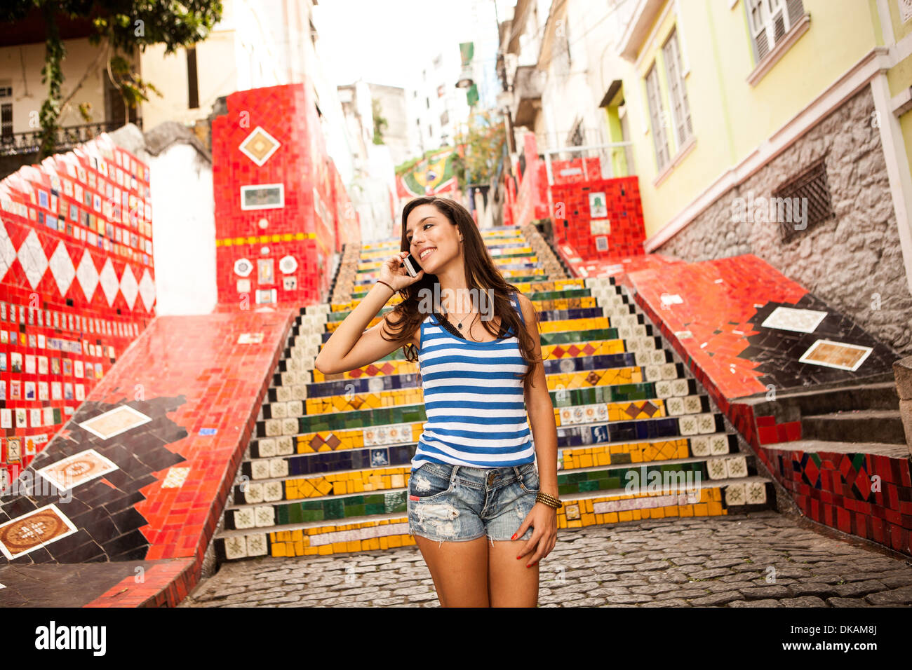 Young woman on phonecall in front of the Escadaria Selaron steps in Rio de Janiero, Brazil - Stock Image