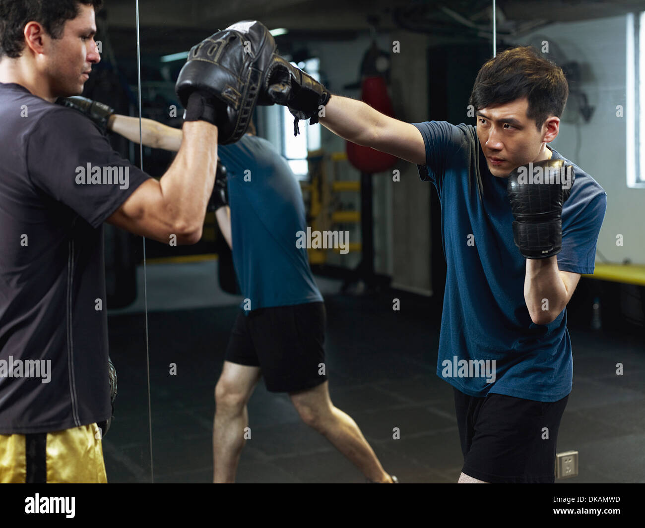 Boxers sparring with gloves and pads - Stock Image