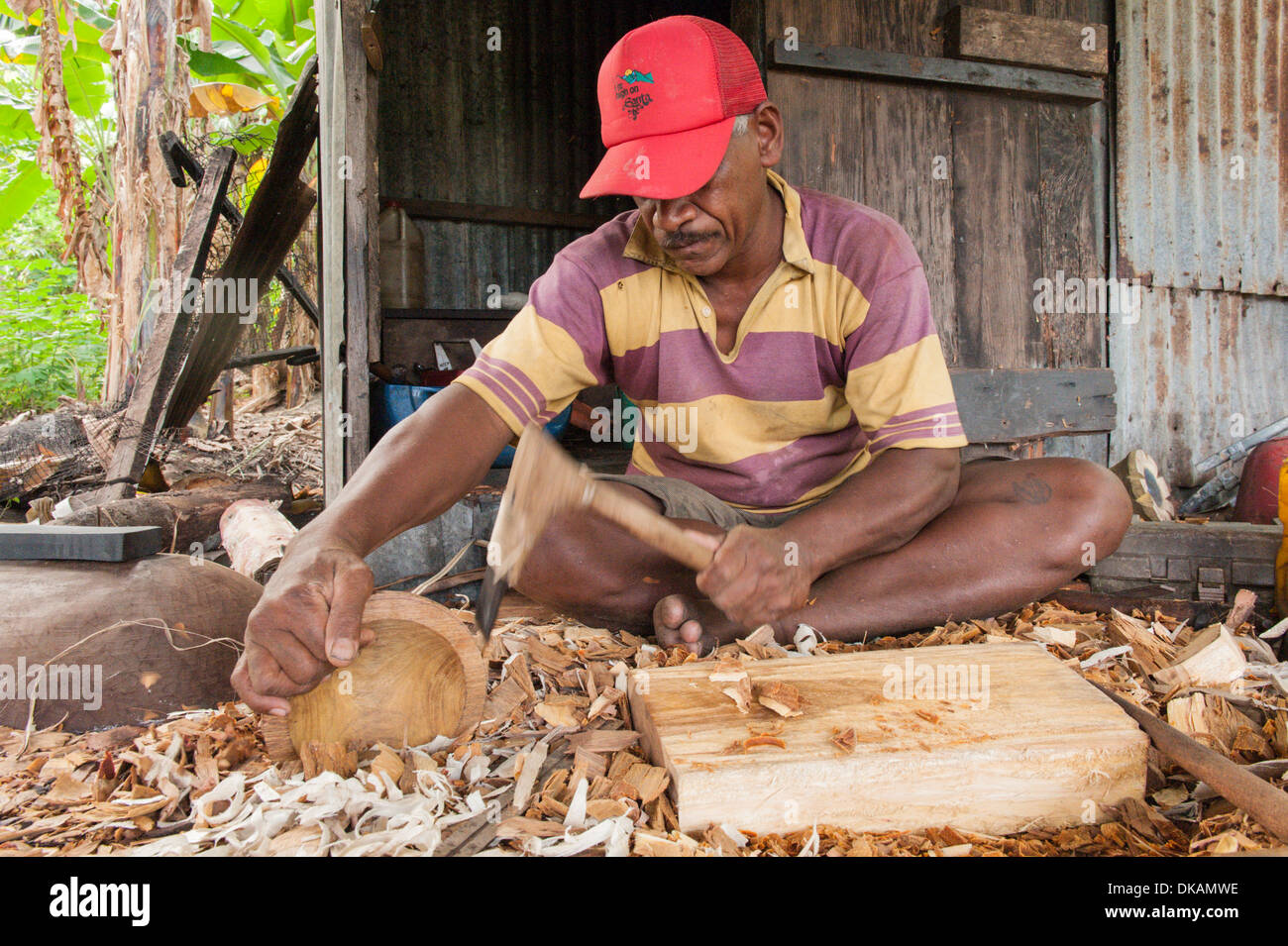 Nico, a wood carver carving tradtional kava bowls out of ...