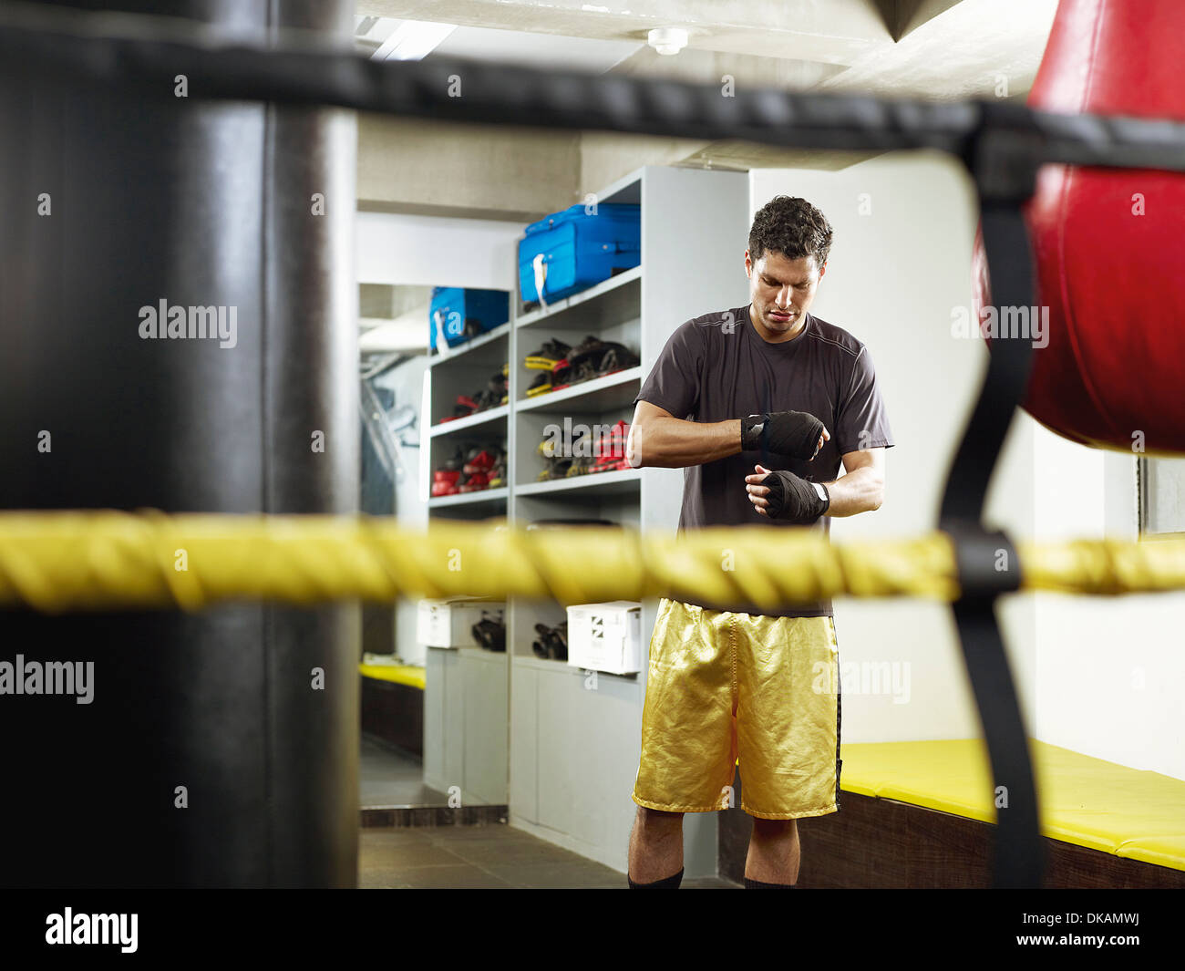 Boxer in changing room taping fists - Stock Image