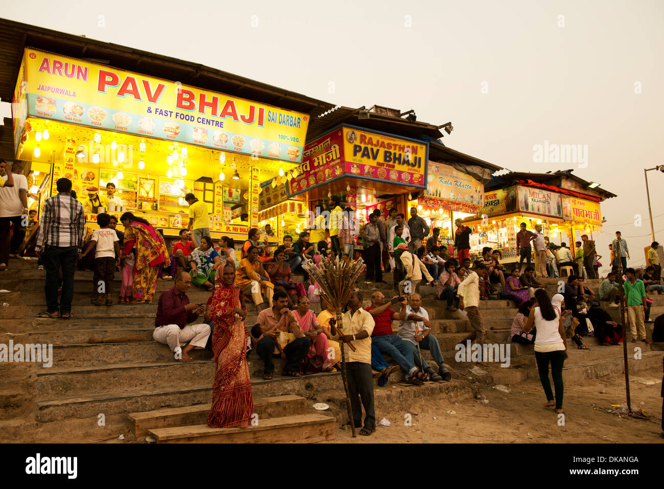 People on the beach in front of food stalls, Juhu Beach. Mumbai, India - Stock Image