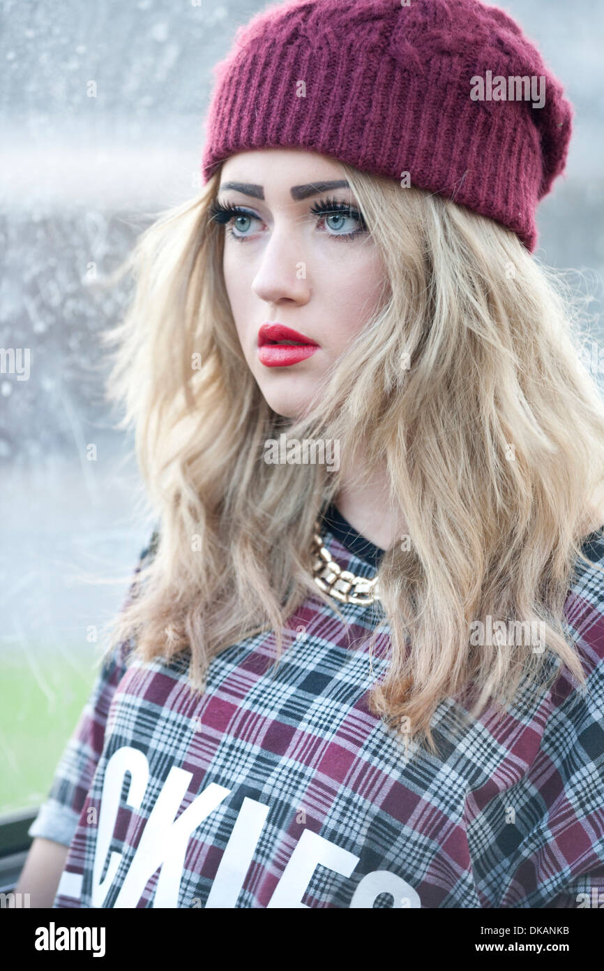 Teenage girl with long blonde hair standing outside at a bus stop. - Stock Image