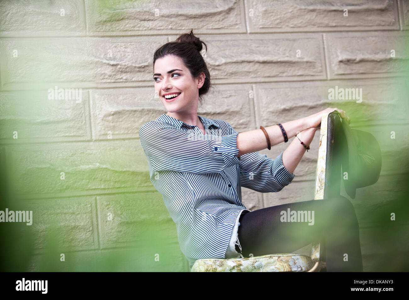 Young woman sitting outside on chair - Stock Image