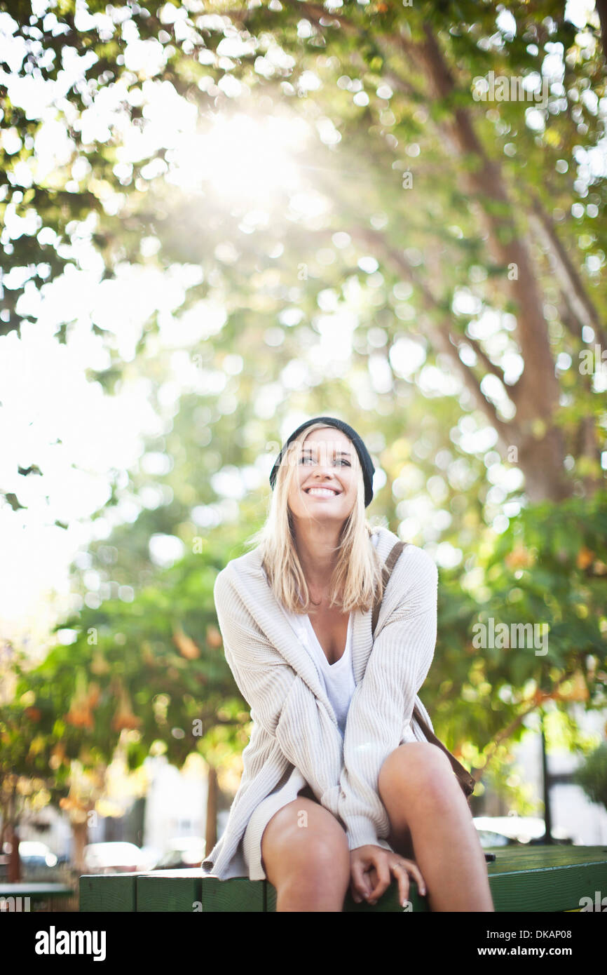 Young woman sitting on bench in park - Stock Image