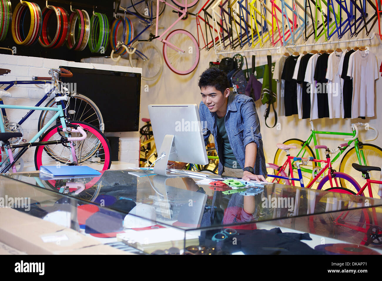 Young man in bike shop using computer - Stock Image