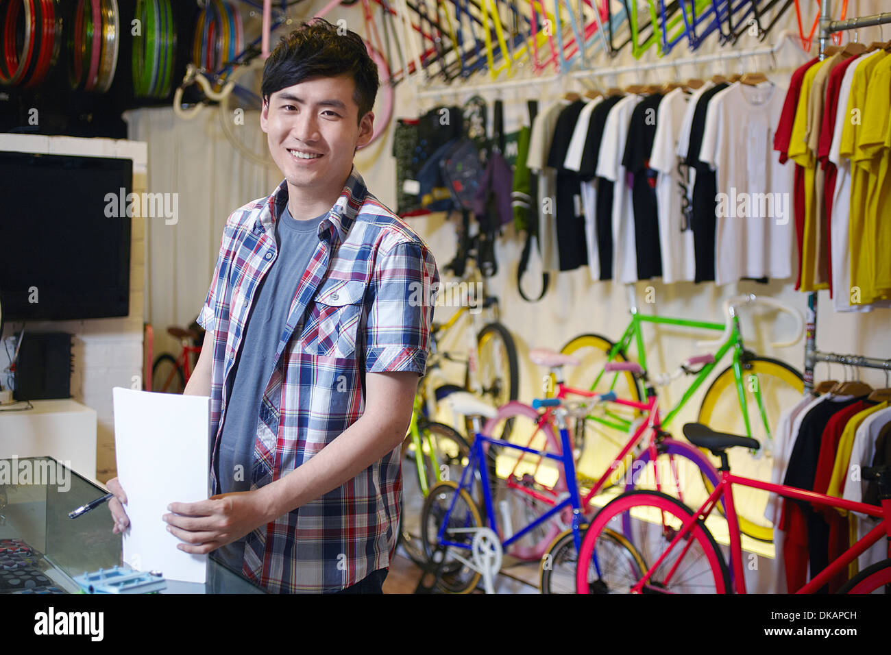 Young man in bike shop holding paperwork - Stock Image