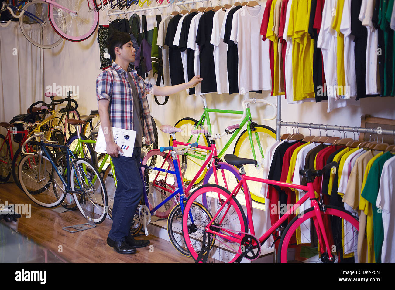 Young man in bike shop choosing t shirt - Stock Image