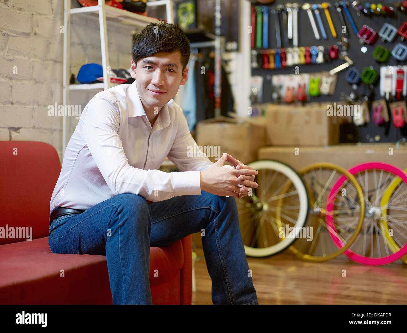 Portrait of young man sitting in bike shop - Stock Image