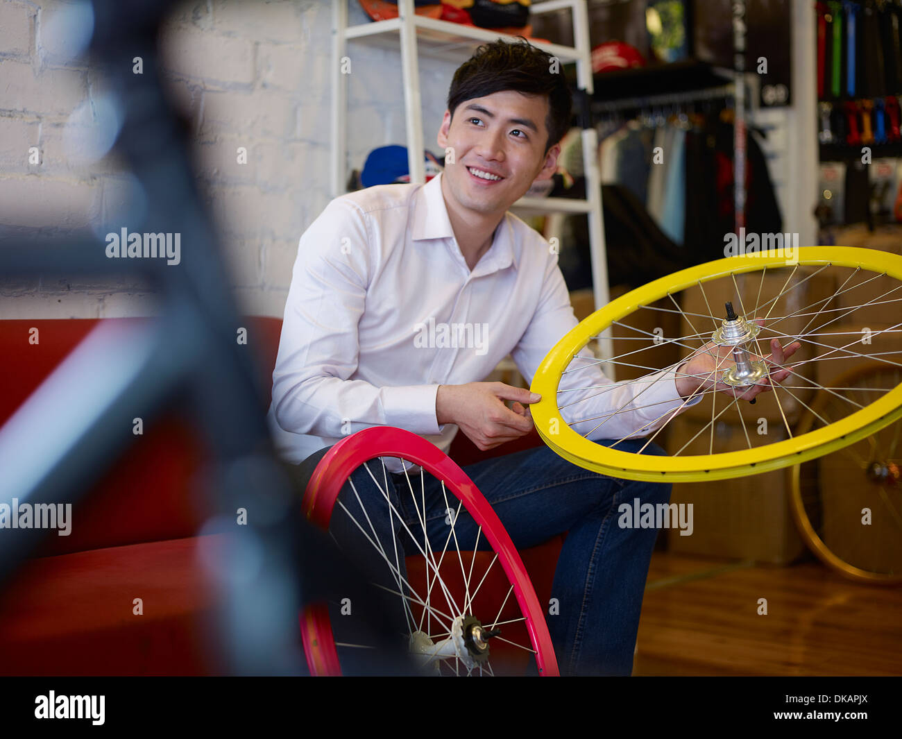 Young man in bike shop holding bicycle wheel - Stock Image