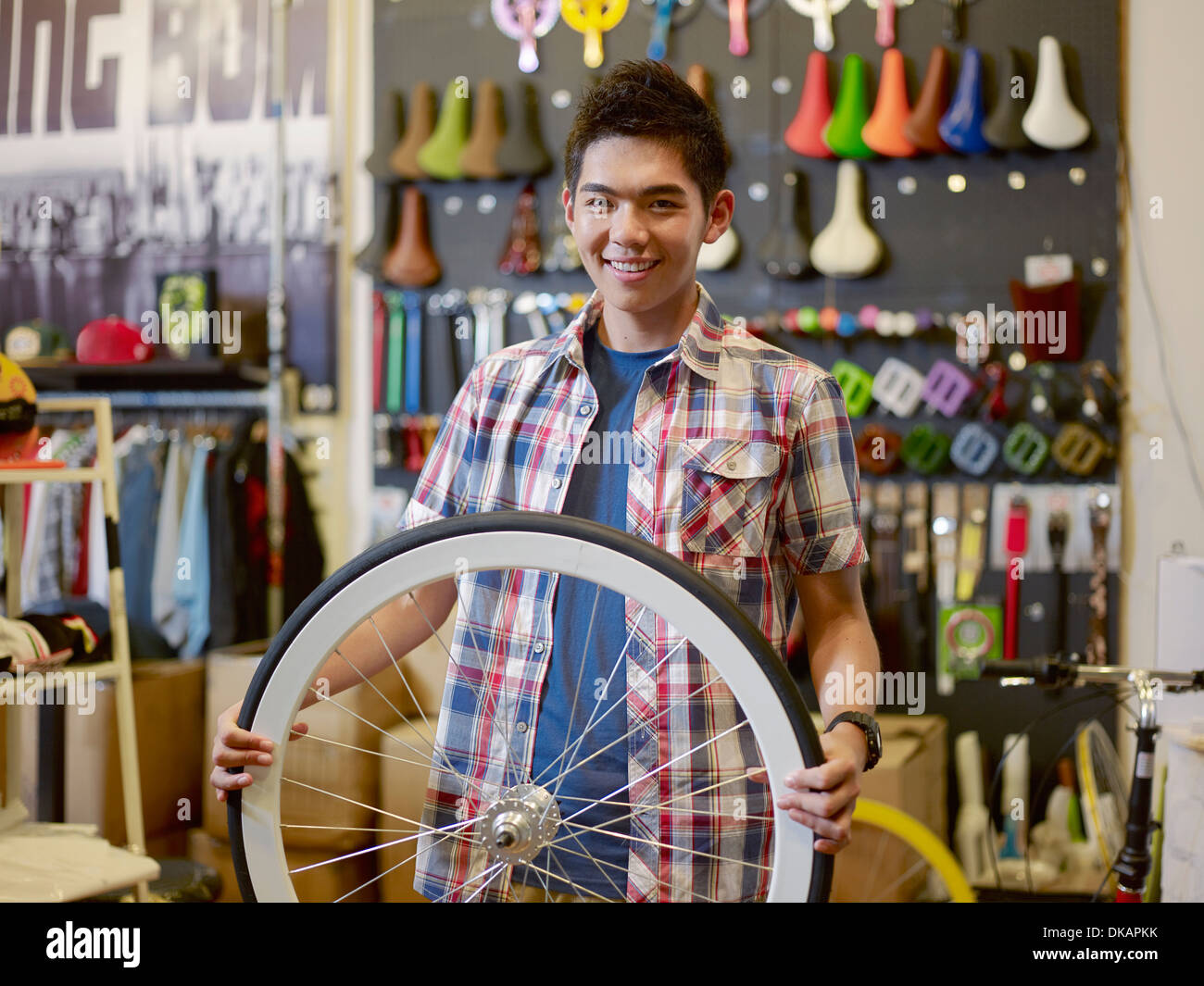 Portrait of young man in bike shop holding bicycle wheel - Stock Image
