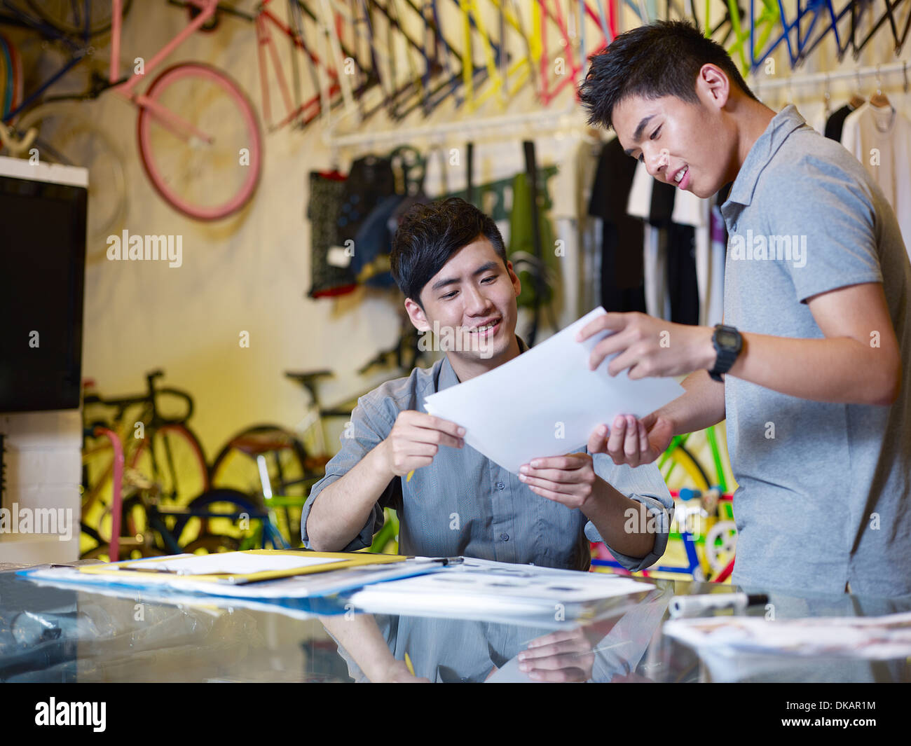 Two young men with paperwork in bike shop Stock Photo
