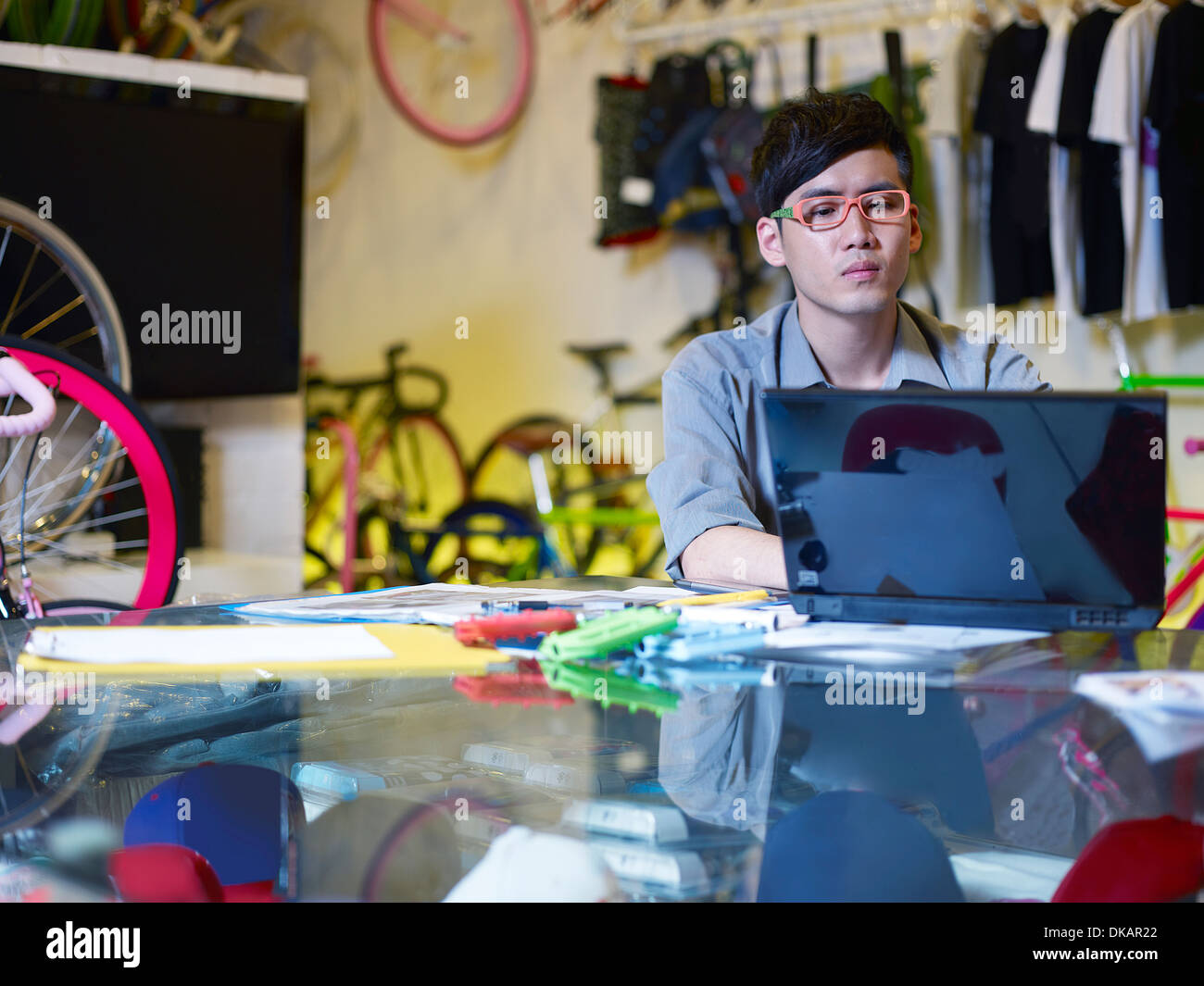 Young man using laptop in bike shop - Stock Image
