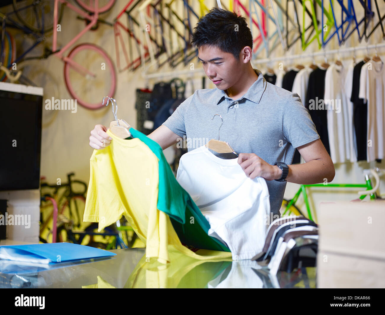 Young man holding t shirts in bike shop - Stock Image
