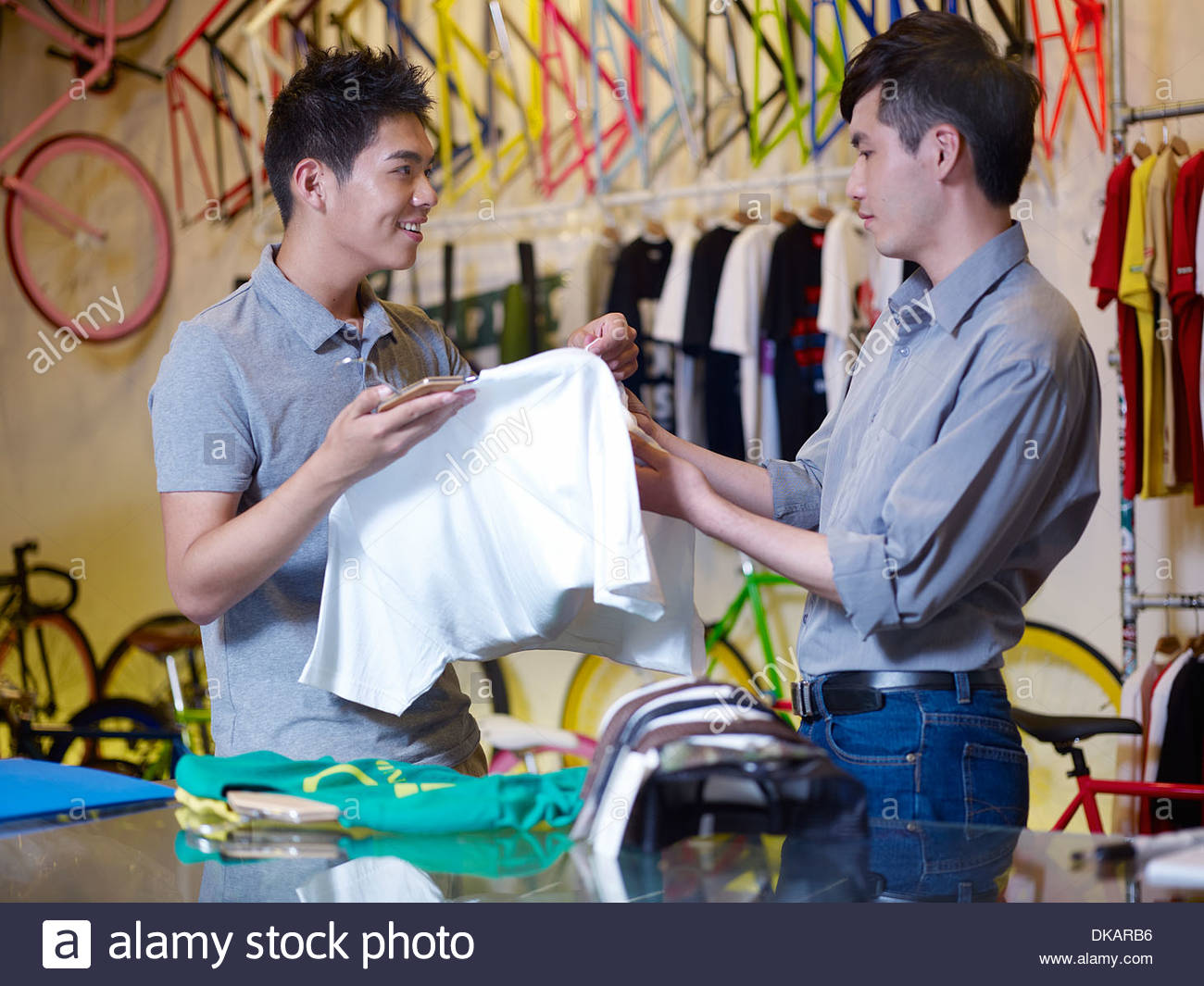 Two young men looking at t shirts in bike shop - Stock Image