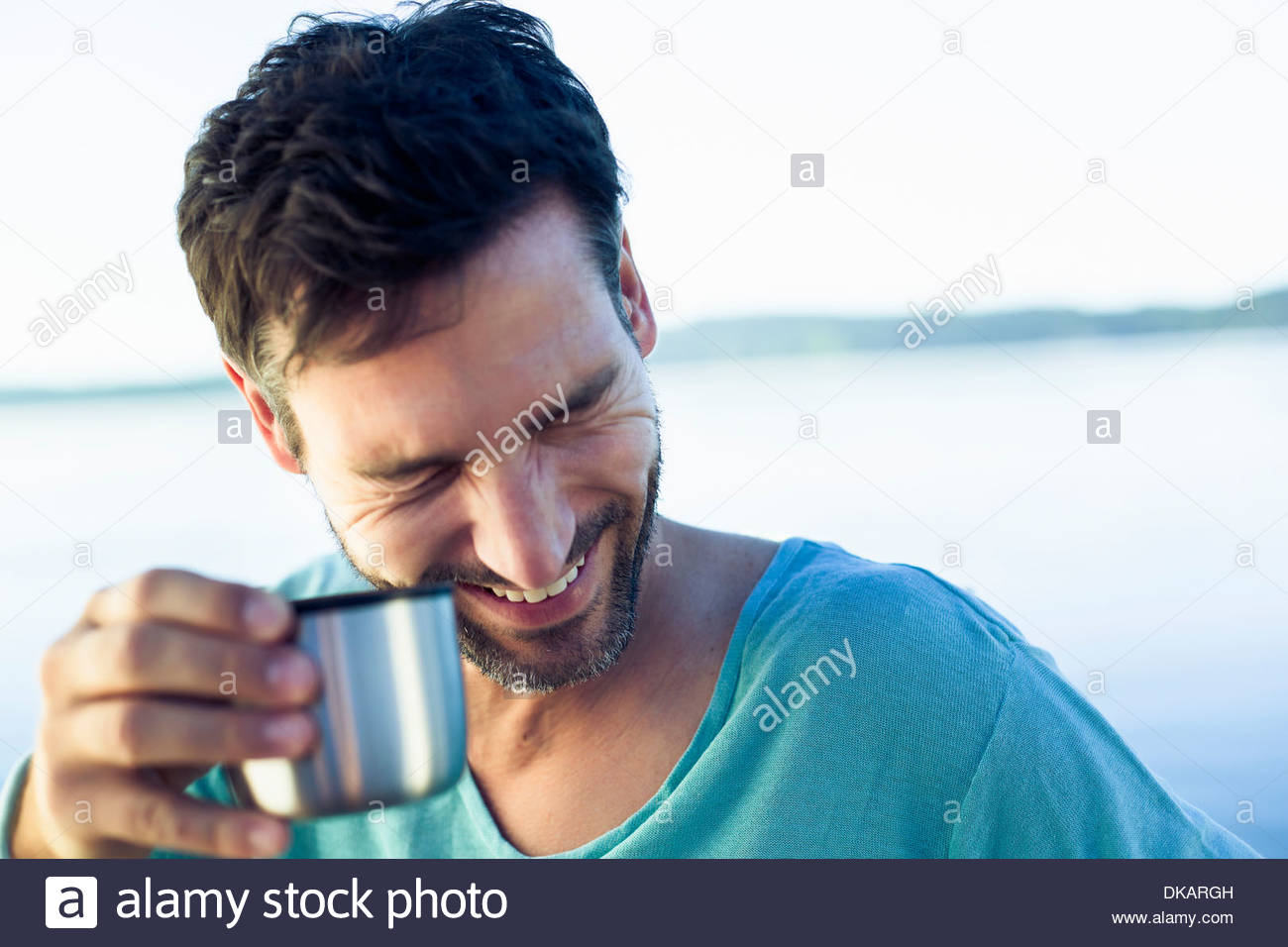 Mature man with coffee, laughing - Stock Image