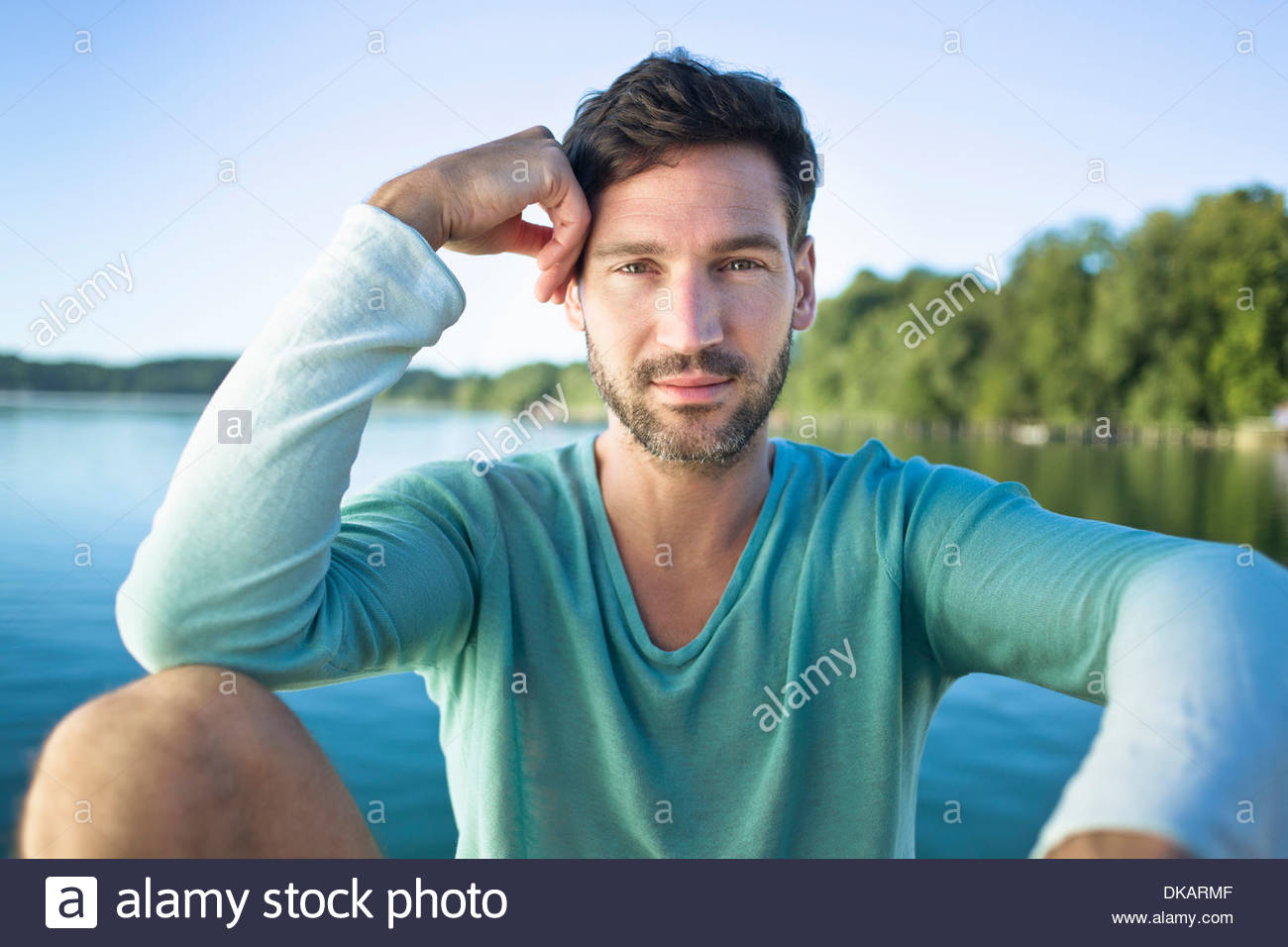 Portrait of mature man leaning on elbow - Stock Image