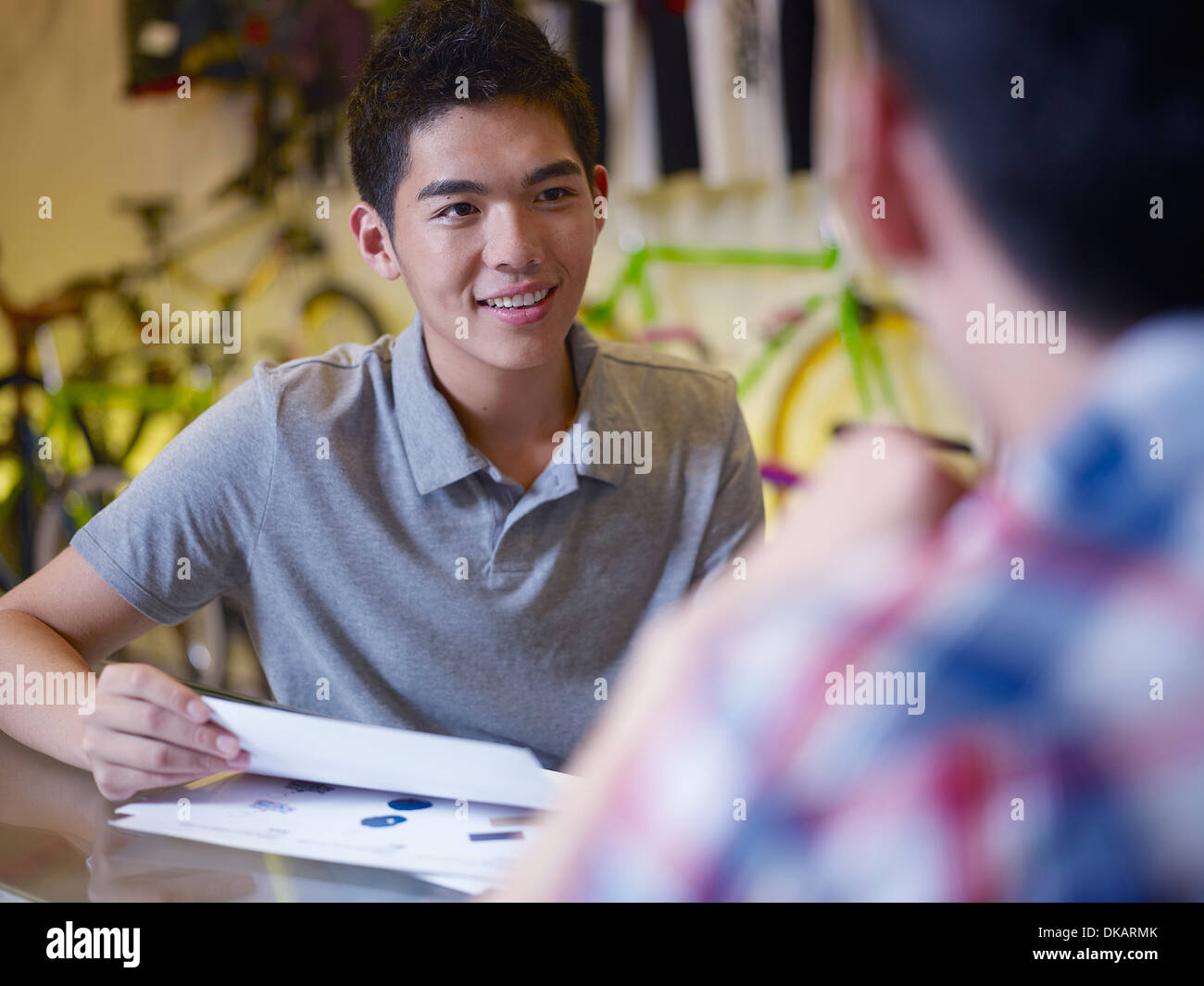 Two young men with paperwork in bike shop - Stock Image