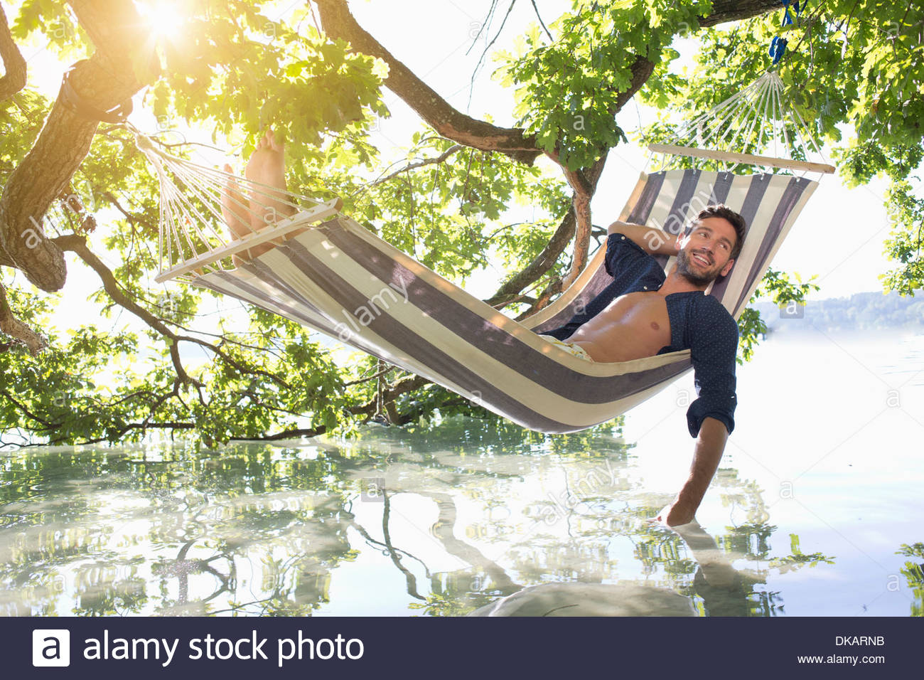 Mature man in hammock dipping hand in lake - Stock Image