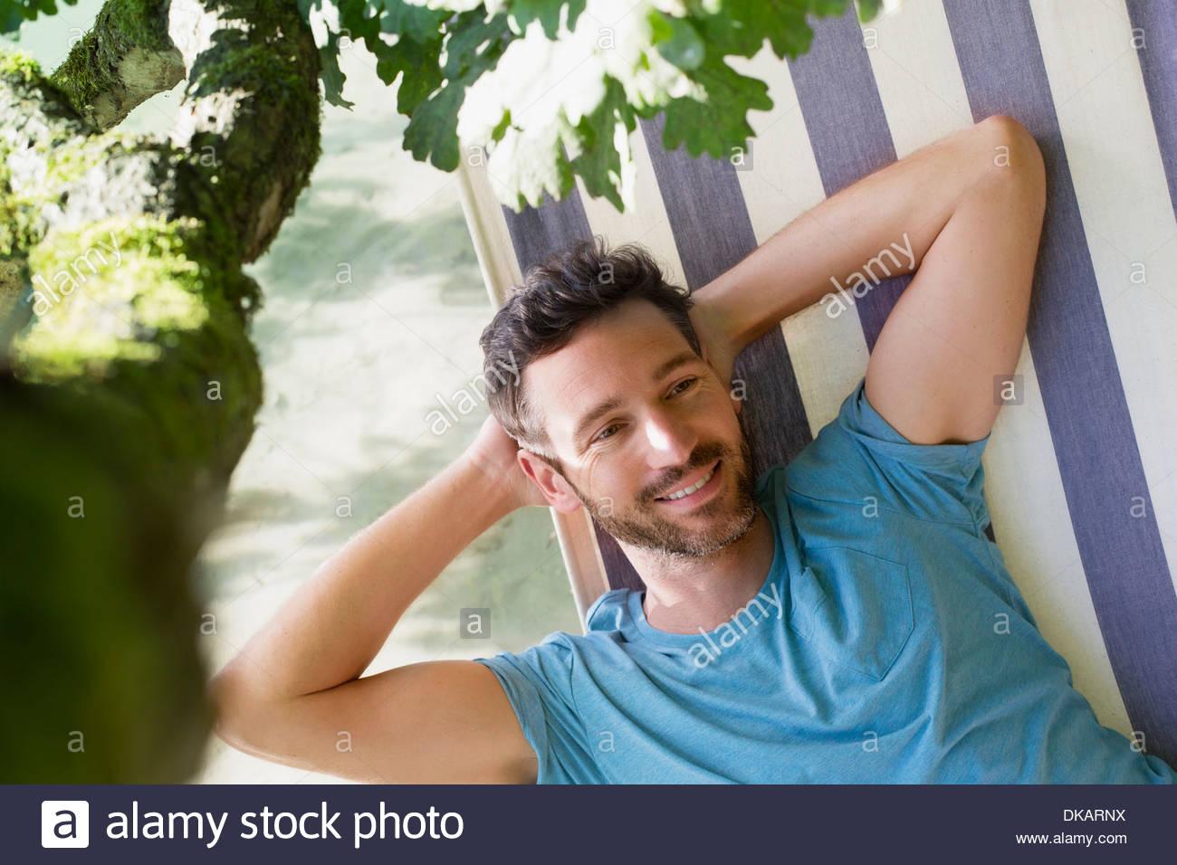 Mature man relaxing in hammock - Stock Image