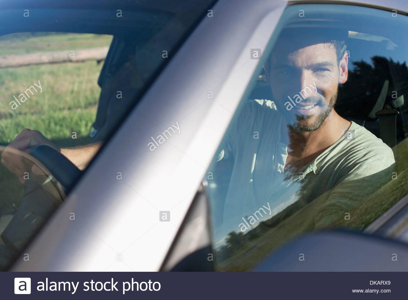 Mature man sitting inside car, smiling - Stock Image