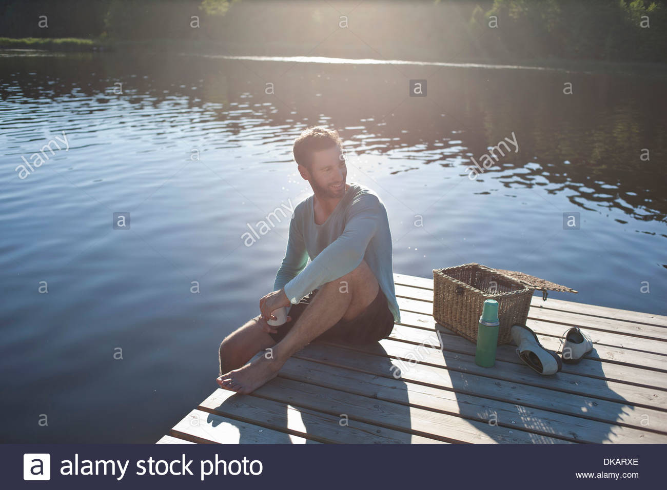 Mature man sitting on decking by lake with picnic hamper - Stock Image