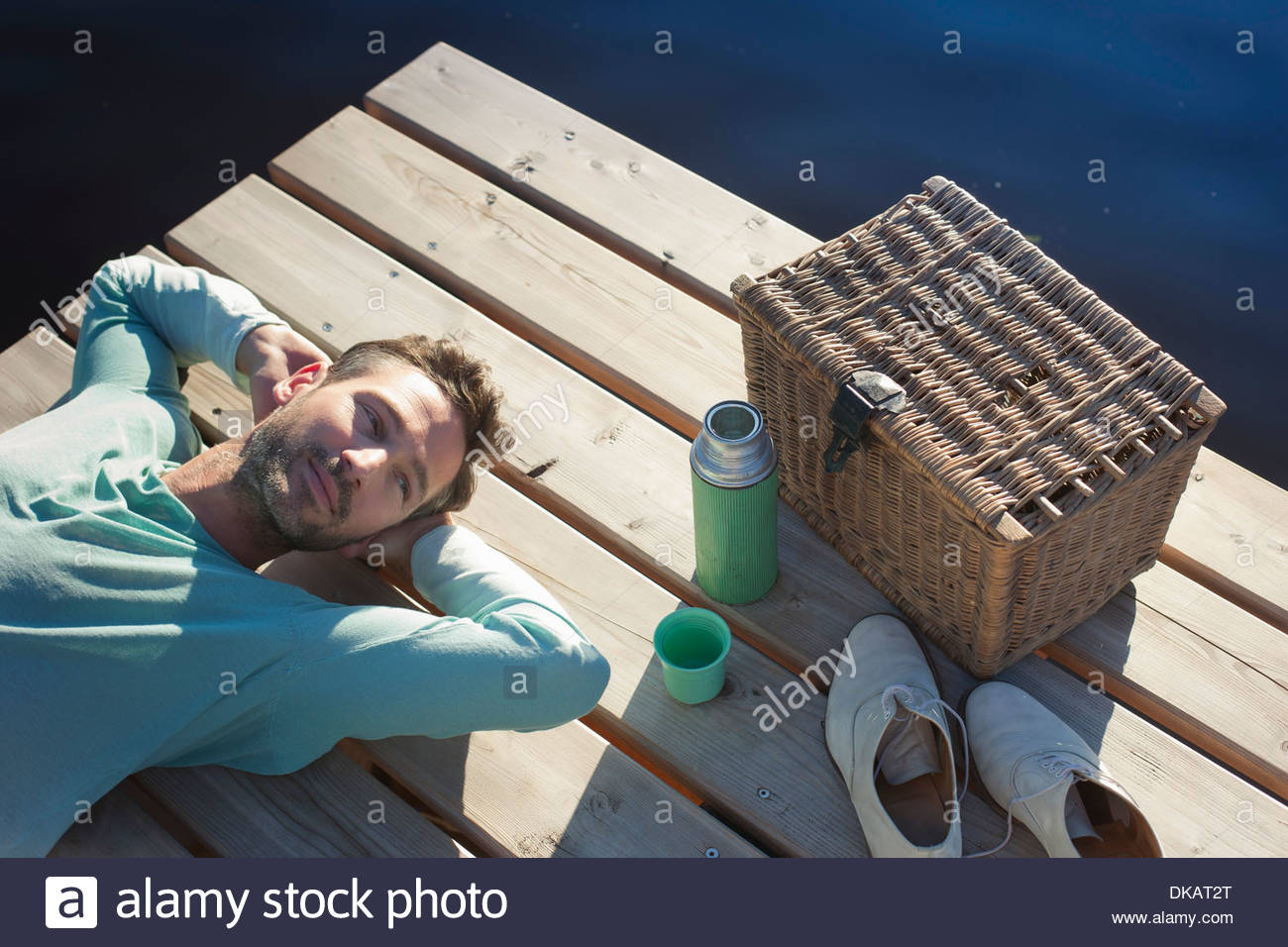 Mature man lying on decking by lake with picnic hamper - Stock Image