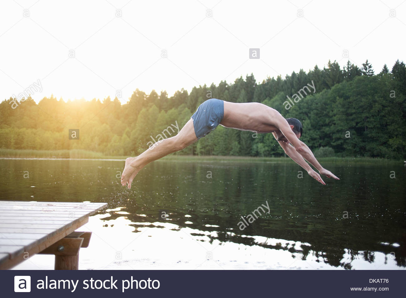Mature man diving into lake - Stock Image
