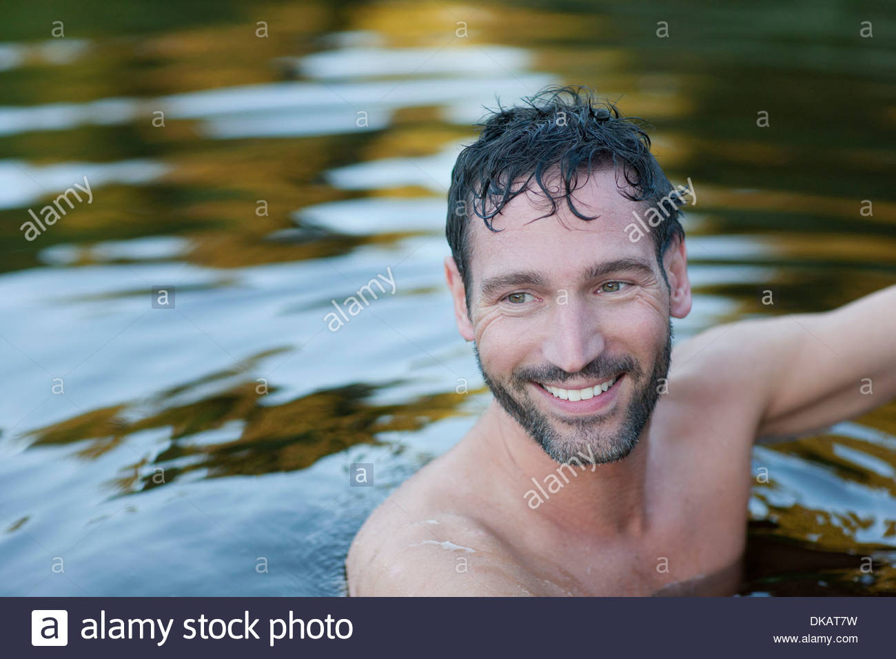 Portait of mature man in lake - Stock Image