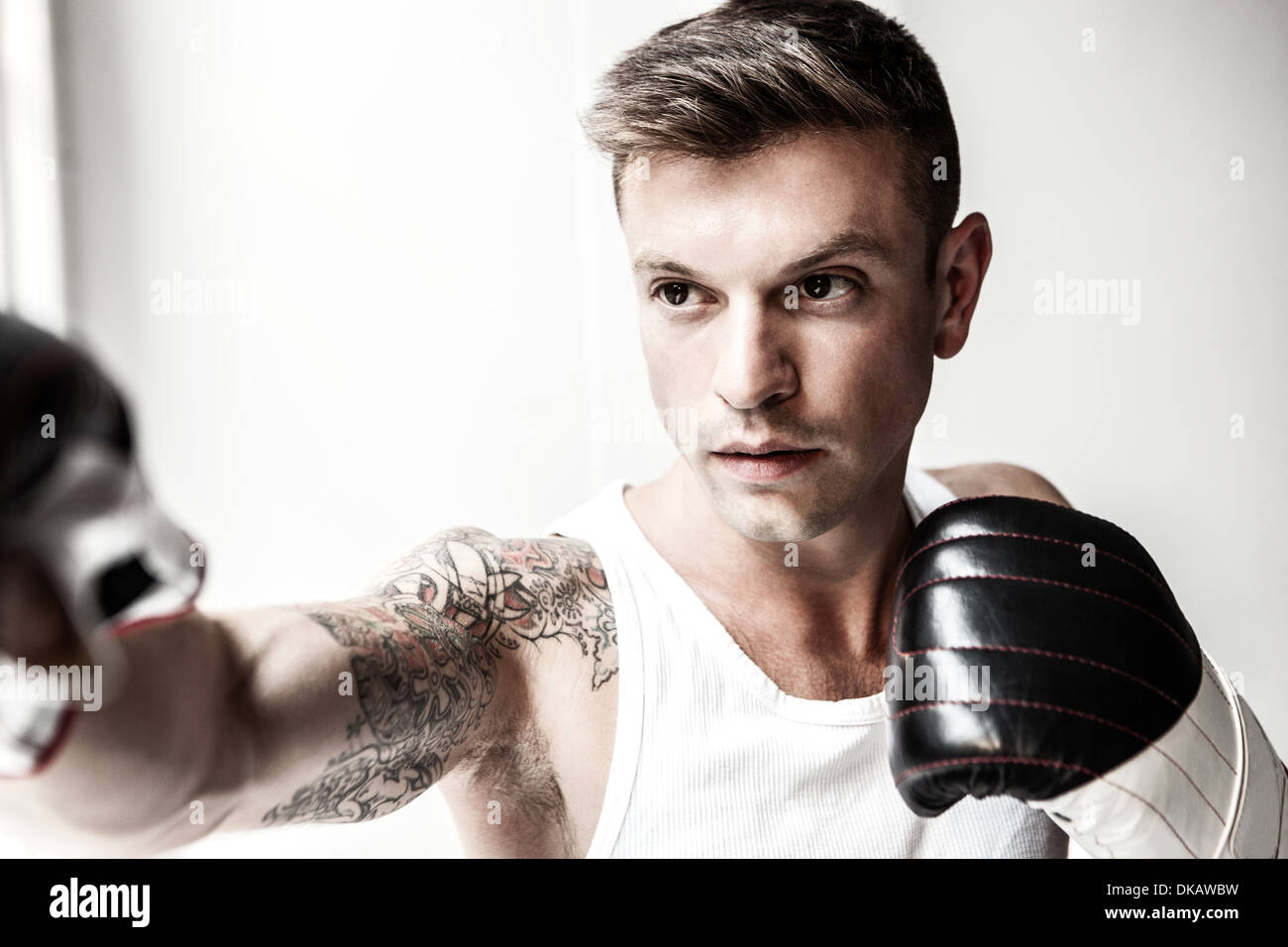 Studio shot of mid adult man boxing - Stock Image