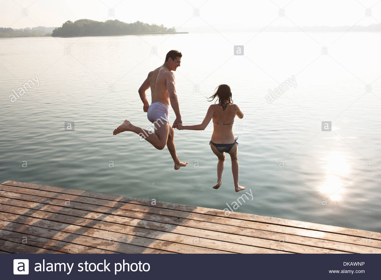 Young couple jumping off lake pier - Stock Image