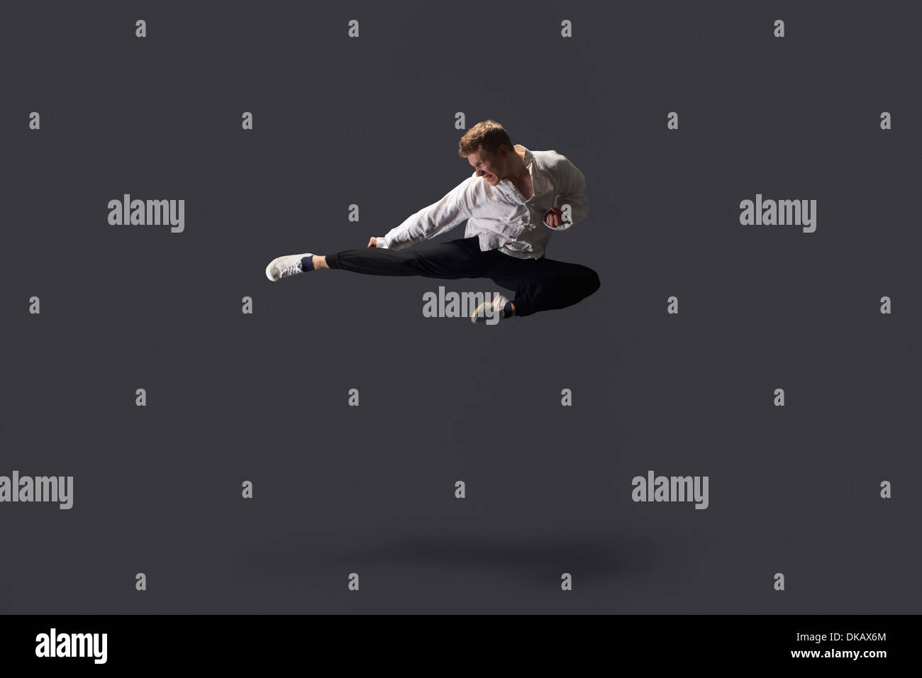 Studio shot of young man mid air practicing martial arts - Stock Image