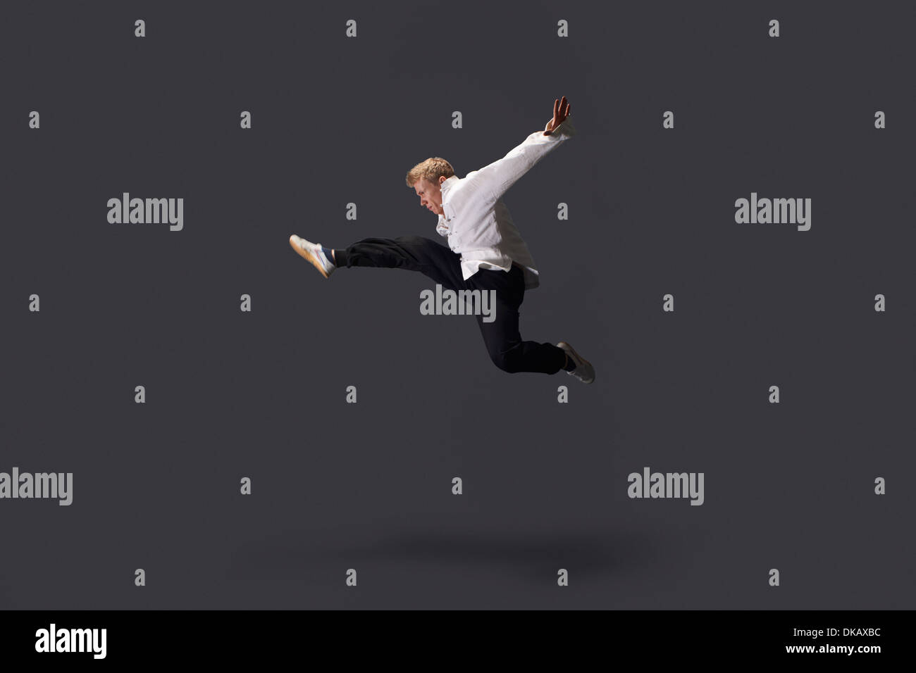 Studio shot of young man practicing martial arts - Stock Image