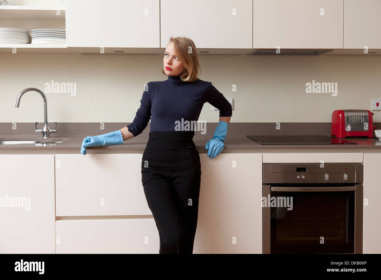 Woman leaning against kitchen cabinet - Stock Image