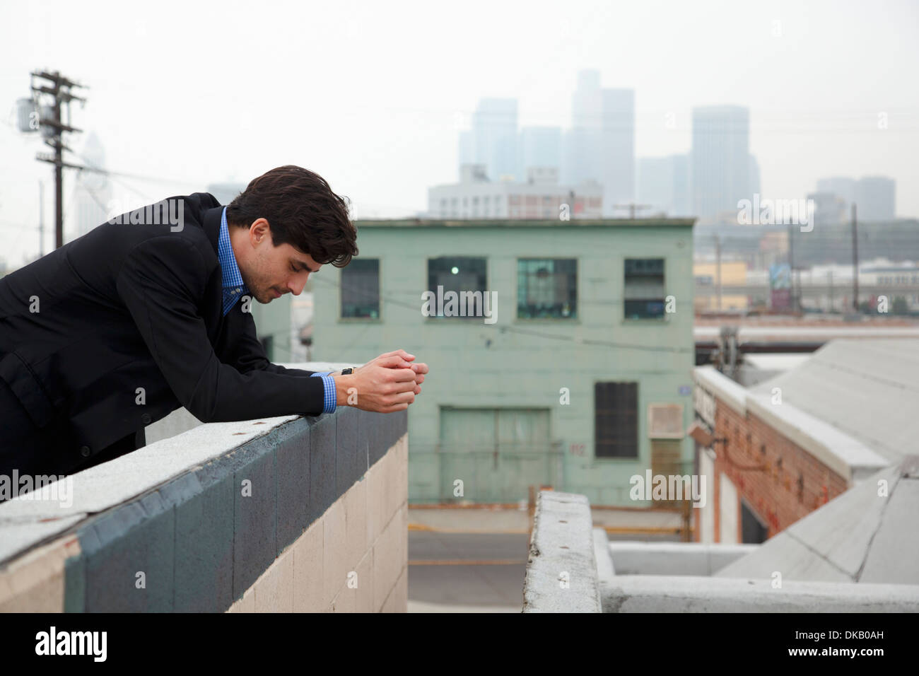 Unhappy young man looking down from city rooftop - Stock Image