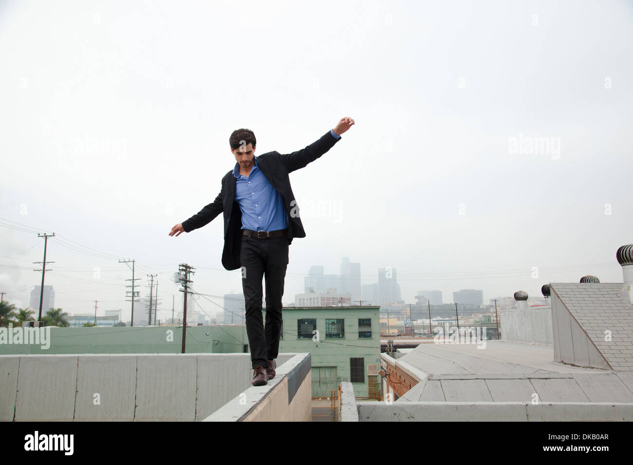 Young man walking wall on city rooftop - Stock Image